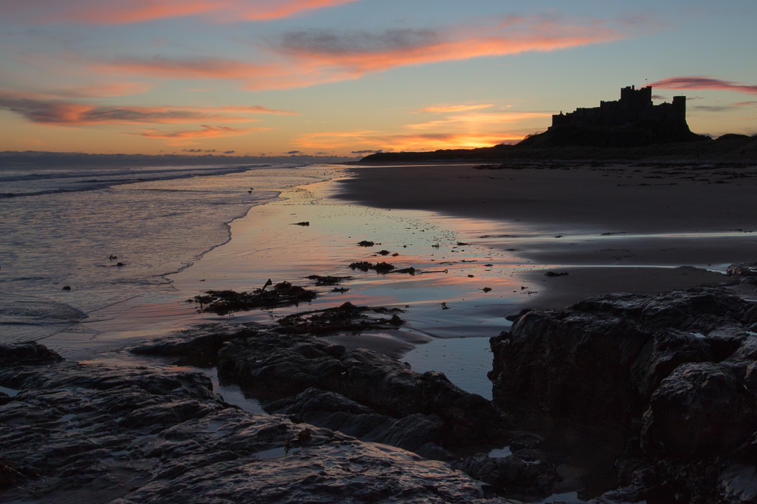 View at dawn of Bamburgh Castle from the beach and rocks, United Kingdom