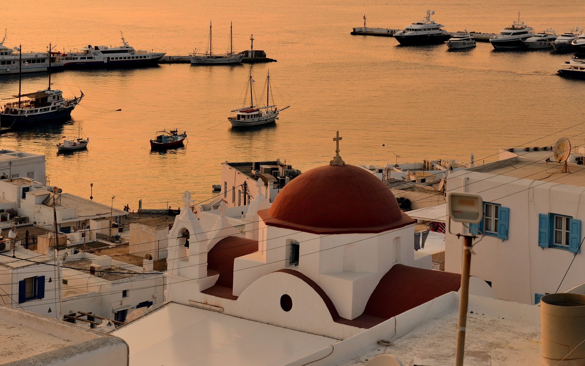 Red dome at sunset in Mykonos old harbour, Greece