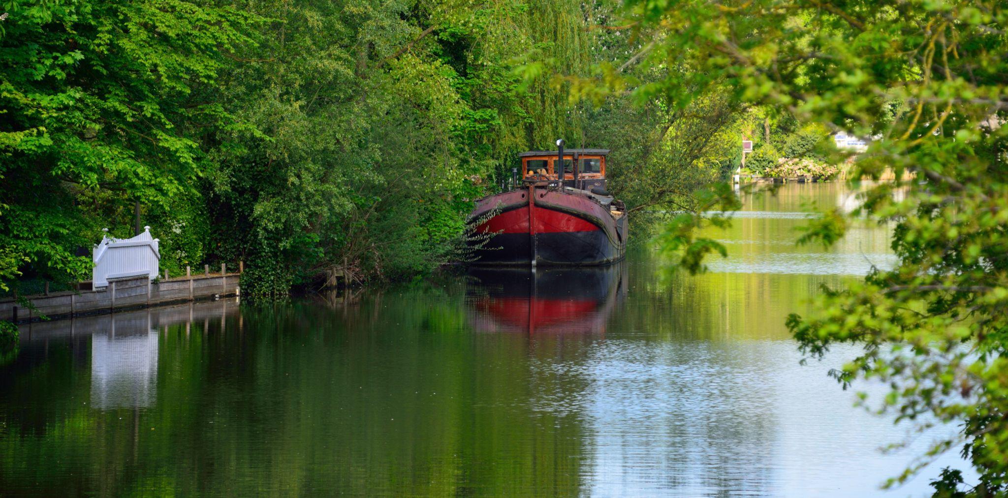 The red boat on the Vecht river, Breukelen, Netherlands