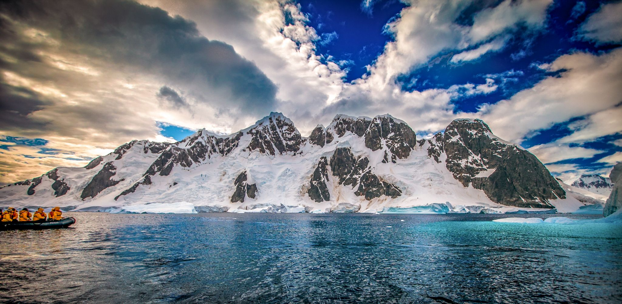 Zodiac with snow covered Island behind, Antarctica